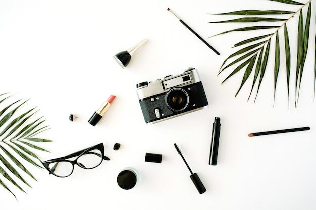 Plat lag vrouwelijke regeling met retro camera, accessoires, glazen, cosmetica en palmtakken op wit