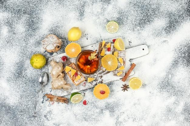 Plat lag wafels en rijstwafels op witte snijplank met kruidenthee, citrusvruchten, kaneel en theezeefje op donkergrijs marmeren oppervlak. horizontaal