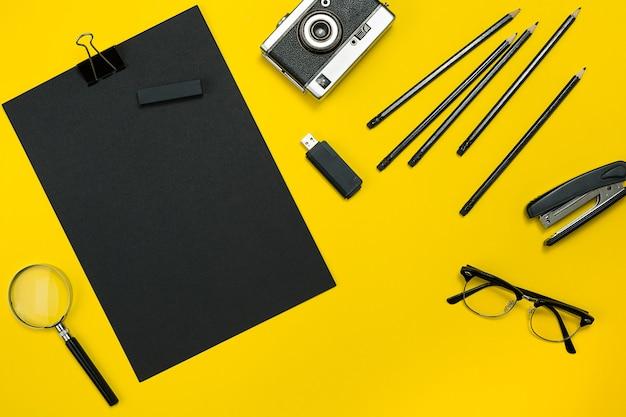 Plat lag weergave van zakelijke kantoorgadgets met kladblok, vintage camera, pen, ontwikkelen, bril en