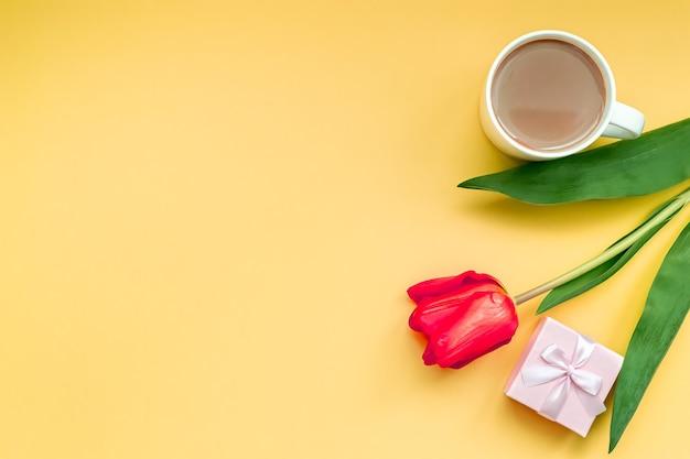 Plat lag wenskaart rode tulp met koffiekopje en cadeau op gele achtergrond