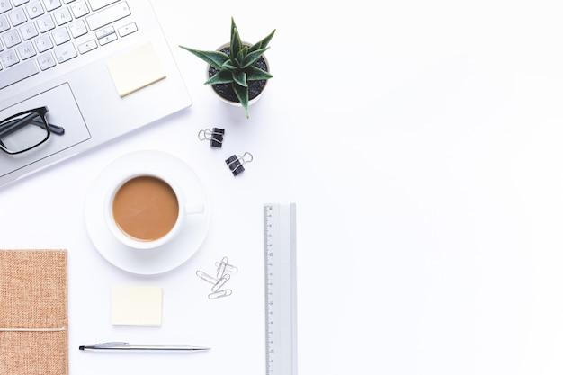 Plat lag, werkplek met laptop, koffie en kantoorbenodigdheden op met bureau. met kopie ruimte.