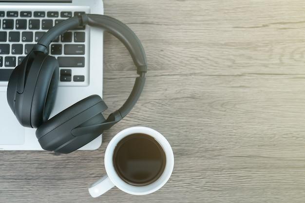 Plat lag werkruimte met koptelefoon, laptop, kopje koffie op houten