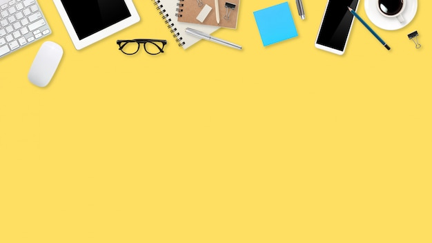Plat lag werkruimte tafel met laptopcomputer, kantoorbenodigdheden, koffiekopje, tablet en mobiele telefoon op gele pastel