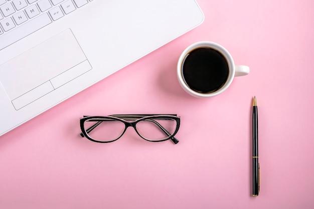 Plat lag werkruimte tafel met witte laptop, kopje koffie en bril, op roze achtergrond.