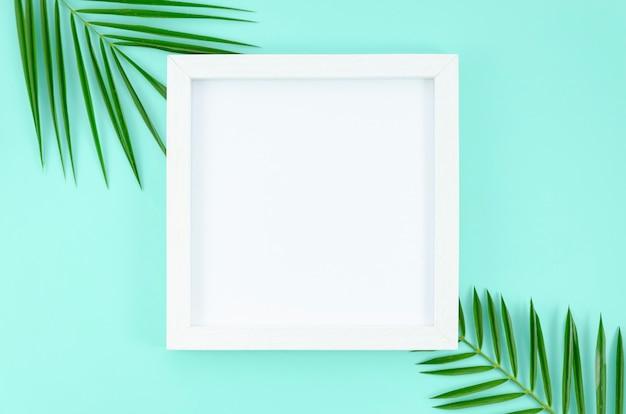 Plat lag wit frame op lichtblauwe achtergrond met palmboom