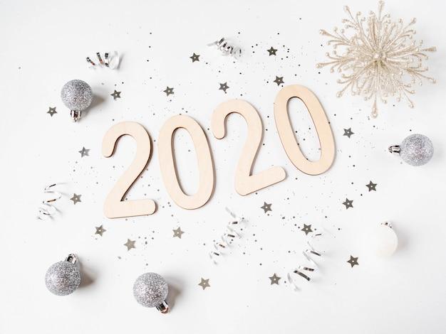 Plat lag wit nieuwjaar samenstelling - nummer 2020, kerstballen, sneeuwvlok, sterren en confetti. bovenaanzicht