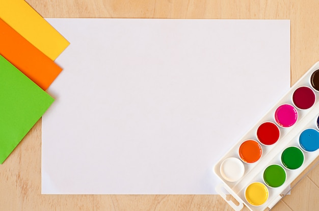 Plat lag wit vel papier, nieuwe aquarelverf, set trending herfstkleuren op houten tafel