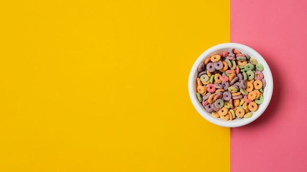 Plat lag witte kom met kleurrijke ontbijtgranen