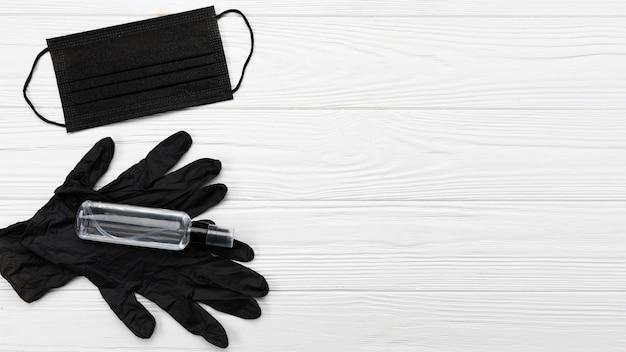 Plat lag zwart medisch masker en handschoenen met kopie-ruimte