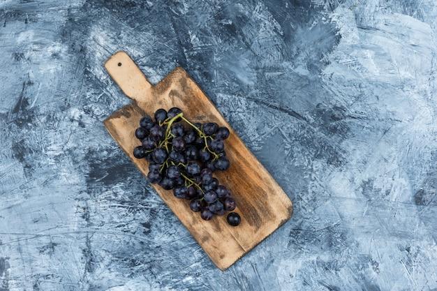 Plat lag zwarte druiven in snijplank op donkerblauwe marmeren achtergrond. horizontaal