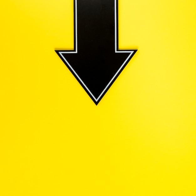 Plat lag zwarte pijl naar beneden op gele achtergrond met kopie-ruimte