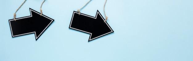 Plat lag zwarte pijlen op blauwe achtergrond met kopie-ruimte