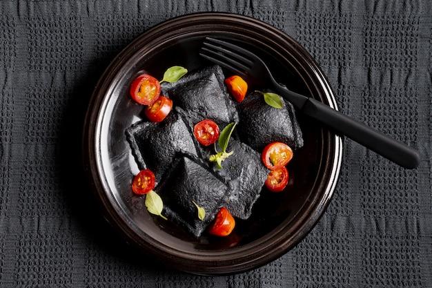 Plat lag zwarte ravioli en plakjes tomaten met kruiden