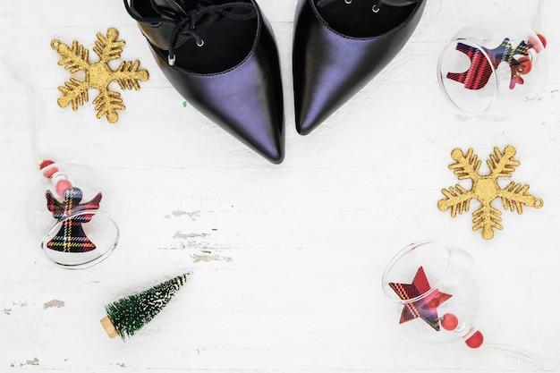 Plat lag zwarte schoenen met hoge hakken, mini-kerstboom en kerstversieringen