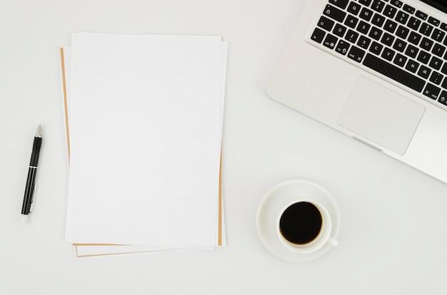 Plat lay-papier mockup naast laptop
