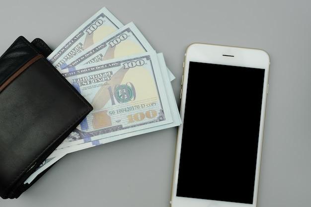Plat lederen portemonnee, bankbiljetten amerikaanse dollars en witte smartphone zwart scherm met kopie ruimte op lichte glay achtergrond.