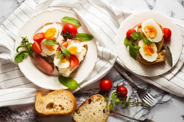 Plat leg hardgekookte eieren met tomaten en hotdog