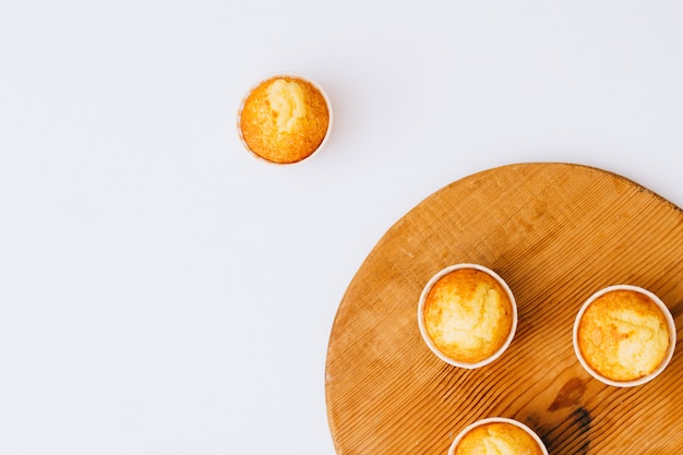 Plat leg minimalisme zelfgemaakte oranje muffins op houten bord
