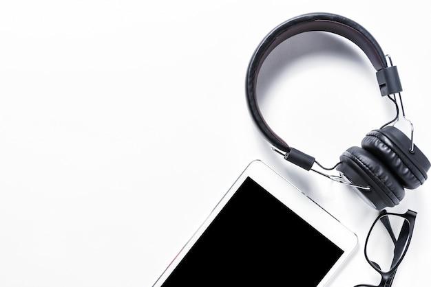 Plat leg van oortelefoon en tablet op witte achtergrond, muziekconcept