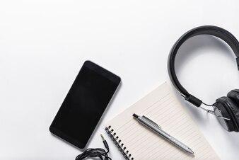 Plat leg van oortelefoon, mobiele telefoon en notitieboekje op witte achtergrond, muziekconcept
