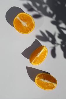 Plat leg verse mandarijnen citrusvruchten met schaduwen op een wit.