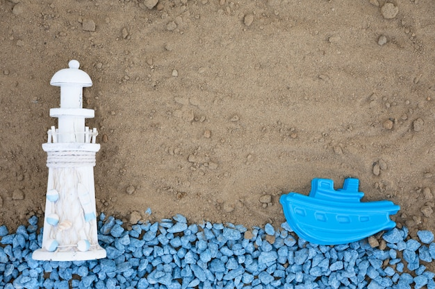 Plat leggen blauwe kiezels met vuurtoren en boot op zand