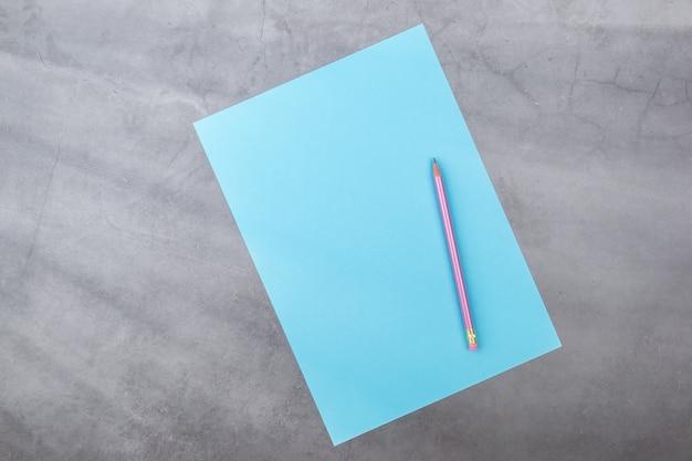 Plat leggen, bovenaanzicht, blauw blad en potlood op een grijze gestructureerde achtergrond