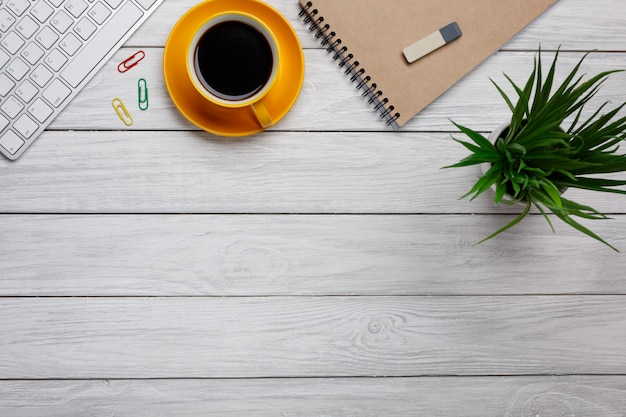 Plat leggen, bovenaanzicht kantoortafel. werkruimte met lege notitie boek, toetsenbord, kantoorbenodigdheden, witte bloemen, groene blad en koffiekopje op witte achtergrond.