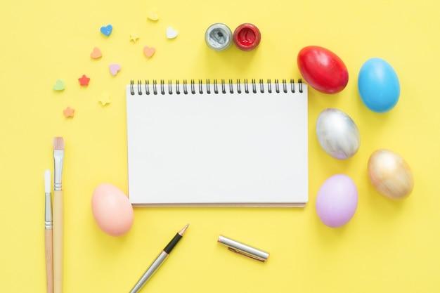 Plat leggen bovenaanzicht kleurrijke easter egg geschilderd in pastel kleuren samenstelling en mock-up lege notebook