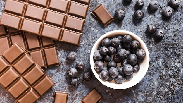 Plat leggen chocolade en bosbessen op grunge tafel