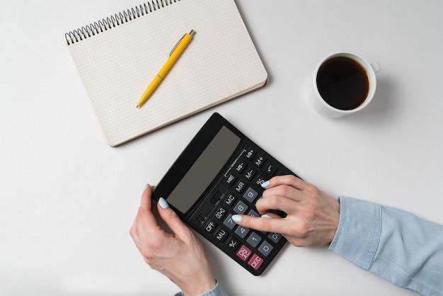Plat leggen. de handen en de calculator van vrouwen dichtbij notitieboekje en kop van koffie.