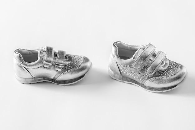 Plat leggen. de zilveren die sportenschoenen van kinderen op een witte achtergrond worden geïsoleerd