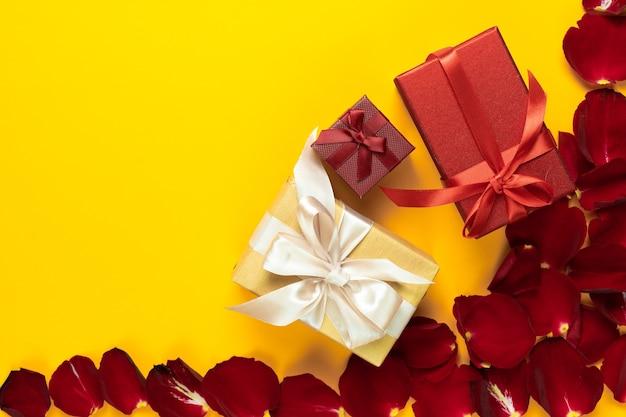Plat leggen, een aantal mooi verpakte dozen liggen in een winkelmandje op een oranje achtergrond bij rozenblaadjes
