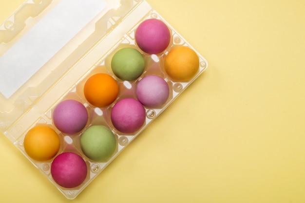 Plat leggen, gekleurde paaseieren in een container.