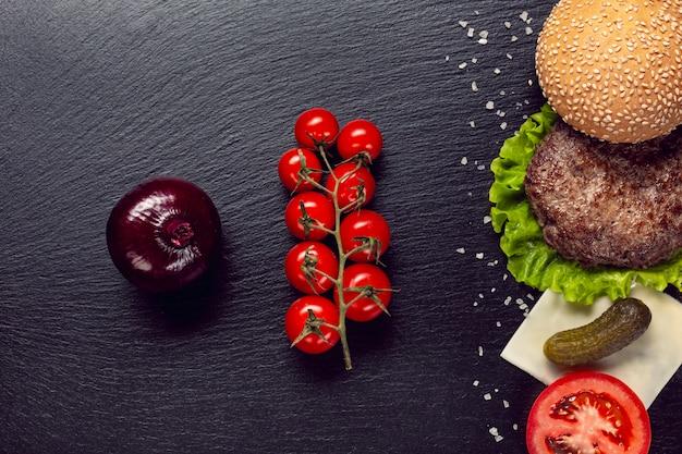 Plat leggen hamburger ingrediënten op leisteen achtergrond