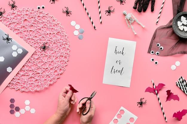 Plat leggen, handen met een schaar en halloween-decor. bovenaanzicht op zeshoekige confetti, papieren rietjes, vleermuizen, suikerharten en spinnen.