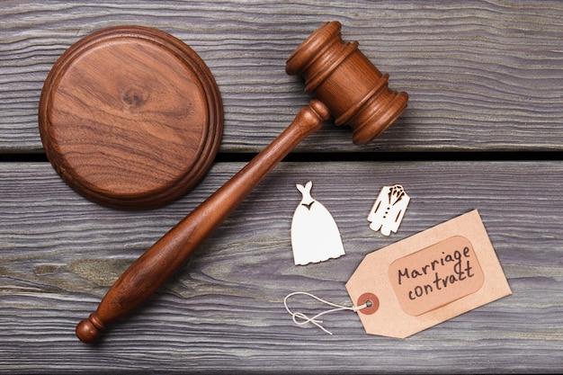 Plat leggen huwelijkscontract en rechtbank concept. houten hamer met miniatuur bruiloftskleding.