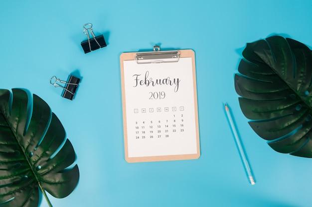 Plat leggen kalender met klembord, palmbladeren en potlood op blauwe achtergrond