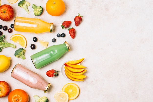Plat leggen kleurrijke smoothies en fruit met kopie ruimte
