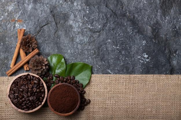 Plat leggen koffiebonen in houten beker op groen blad, den op jute op zwarte steen
