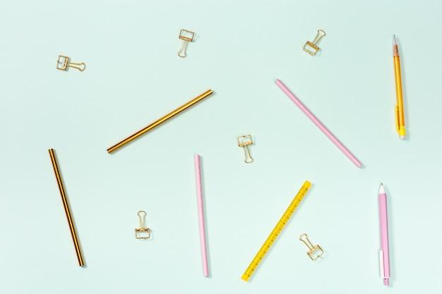 Plat leggen met briefpapier voor school of kantoor. roze en gouden kleurpotloden, pennen en metalen paperclips.