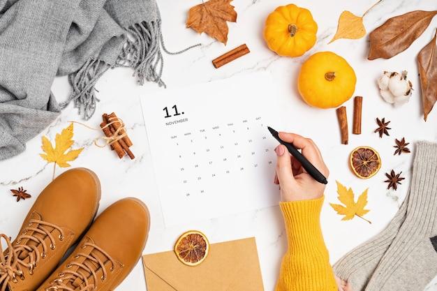 Plat leggen met kalender voor november met herfstaccessoires voor damesmode. social media blog, schema, planning, thanksgiving concept. flatlay, bovenaanzicht