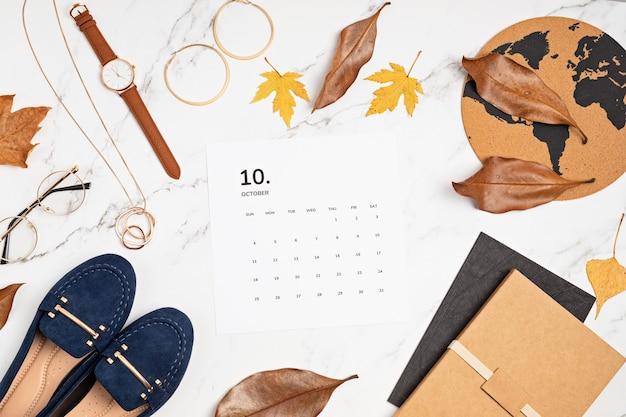 Plat leggen met kalender voor oktober met herfstmodeaccessoires voor dames. social media blog, schema, planning, herfstconcept. flatlay, bovenaanzicht