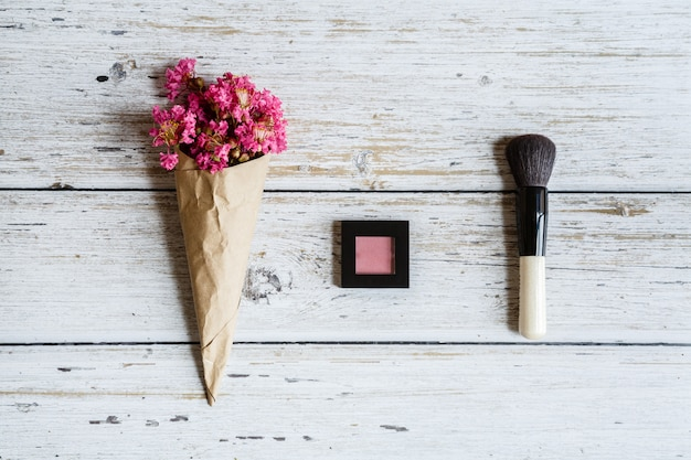 Plat leggen met make-up blozen, penseel en bloemen op houten tafel