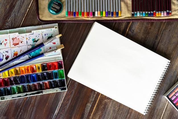 Plat leggen met potloden, penselen, aquarelverf, papier en krijt pastelkrijt