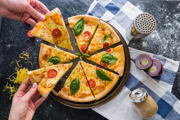 Plat leggen met traditionele italiaanse pizza. handen nemen plakjes pizza.