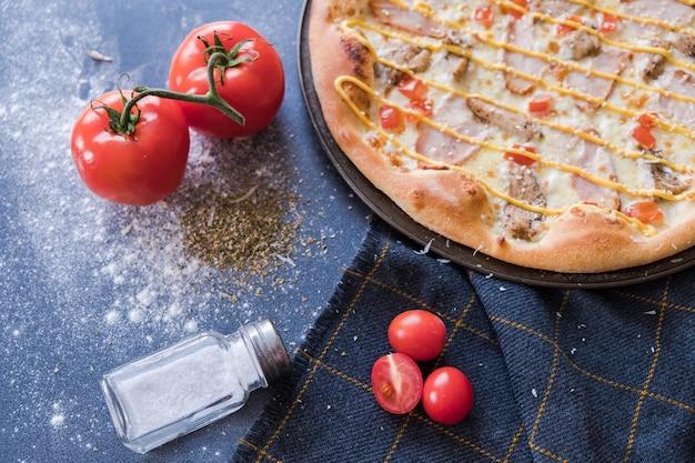Plat leggen met traditionele italiaanse pizza met kip op donkerblauwe stenen tafel