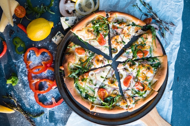 Plat leggen met traditionele italiaanse pizza met mosselen, rucola en parmezaan op donkerblauwe stenen tafel