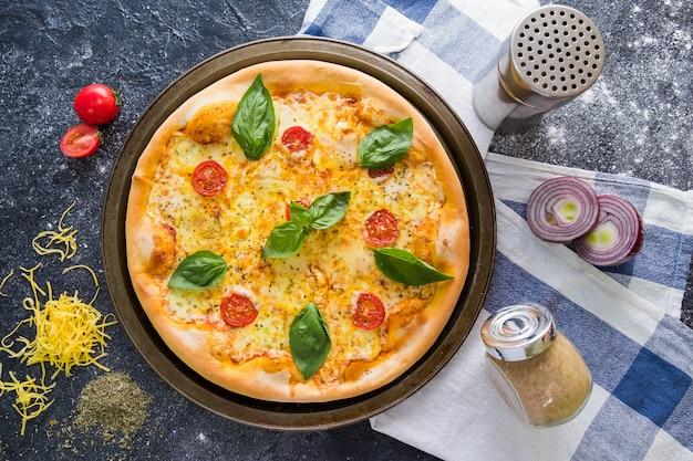Plat leggen met traditionele italiaanse pizza met tomaten, basilicum, mozzarella op donkere stenen tafel
