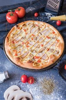 Plat leggen met traditionele italiaanse pizza op donkerblauwe stenen tafel en verschillende ingrediënten